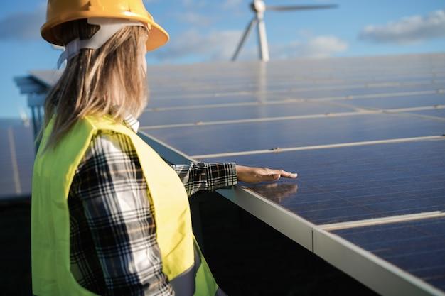 Jovem mulher trabalhando em uma fazenda de energia alternativa - foco no arquiteto entregando o painel solar