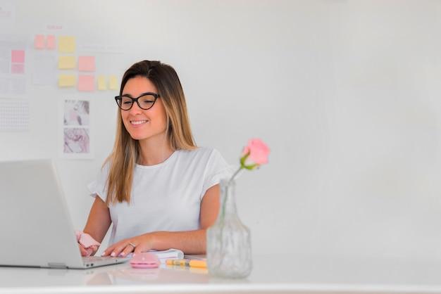 Jovem mulher trabalhando no escritório a sorrir