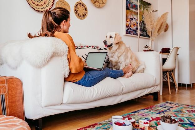 Jovem mulher trabalhando no laptop em casa. cão bonito retriever dourado além disso.