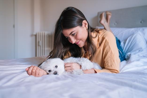 Jovem mulher trabalhando no laptop em casa. cão maltês bonito além