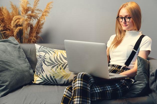 Jovem mulher trabalhando no laptop em casa, sentada no sofá. conceito durante o coronavírus
