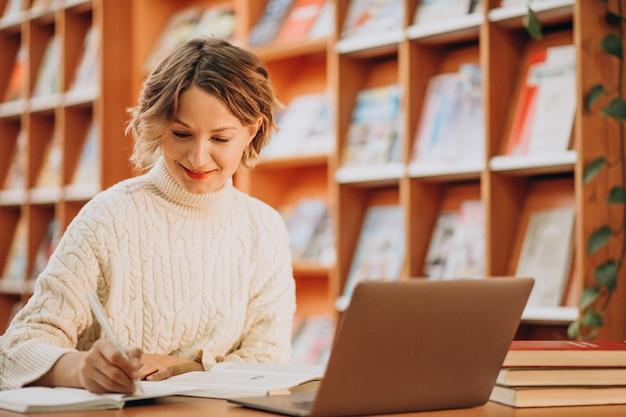 Jovem mulher trabalhando no laptop em uma biblioteca