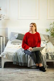 Jovem mulher trabalhando no laptop, sentada na cama em casa. trabalhe em casa durante a quarentena. rapariga com uma camisola e calça jeans em casa na cama