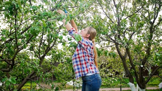 Jovem mulher trabalhando no pomar e cortando galhos de árvores.