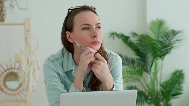 Jovem mulher trabalhando, usando laptop com a mão no queixo, pensando, expressão pensativa