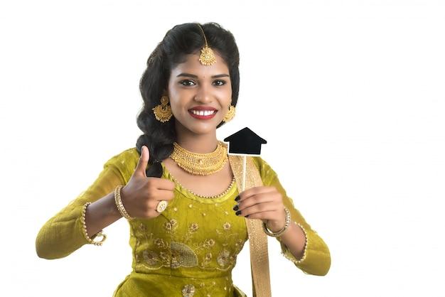 Jovem mulher tradicional indiana feliz que guarda uma placa pequena do entalhe da casa em suas mãos em uma parede branca.