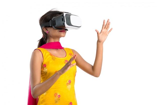 Jovem mulher tradicional indiana que guarda e que mostra o dispositivo de vr, caixa do vr, óculos de proteção, auriculares dos vidros da realidade virtual 3d, mulher com tecnologia futura da imagem latente moderna no branco.