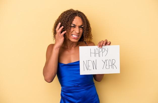 Jovem mulher transexual latina comemorando o ano novo isolado em fundo amarelo, cobrindo as orelhas com as mãos.