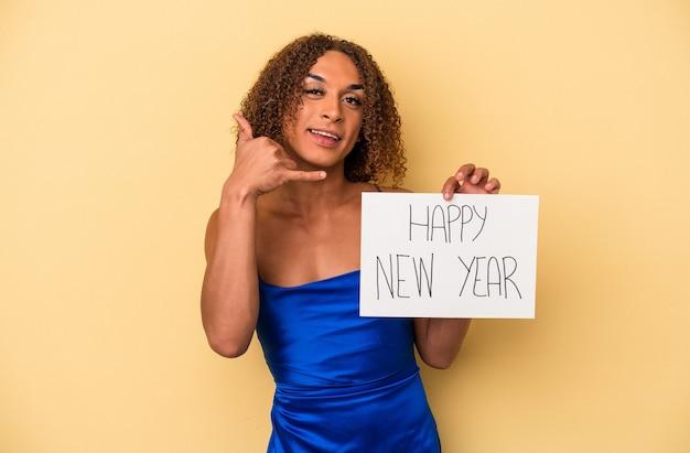 Jovem mulher transexual latina comemorando o ano novo isolado em fundo amarelo, mostrando um gesto de chamada de telefone móvel com os dedos.