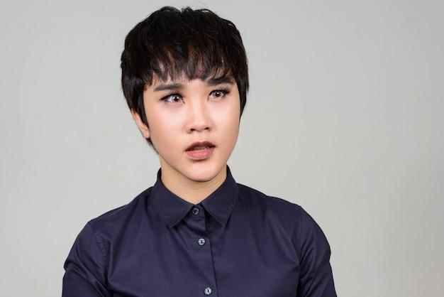 Jovem mulher transgênero asiática andrógina contra uma parede branca