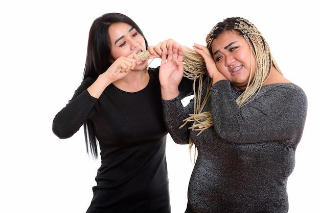 Jovem mulher transgênero asiática comendo e puxando o cabelo de sua amiga