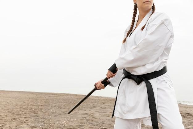 Jovem mulher treinando com roupa de karatê