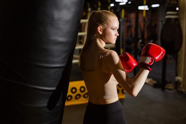 Jovem mulher treinando esportes perto de um saco de pancadas