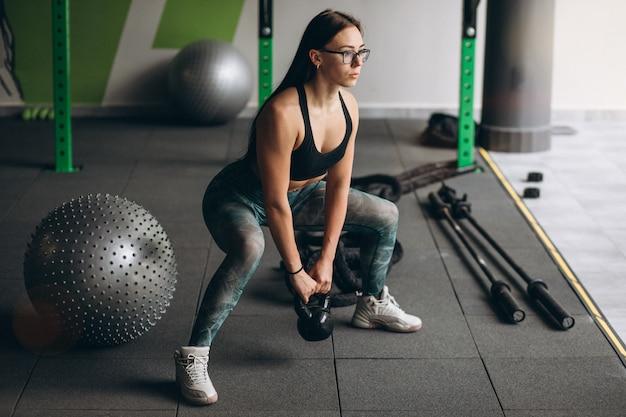 Jovem mulher treinando na academia com equipamento