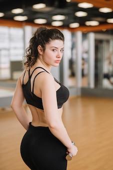 Jovem mulher treinando na academia