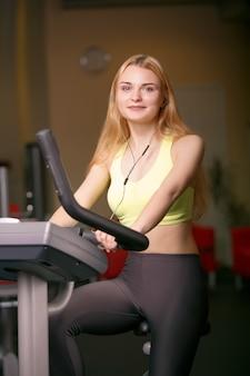 Jovem mulher treinando na bicicleta no ginásio