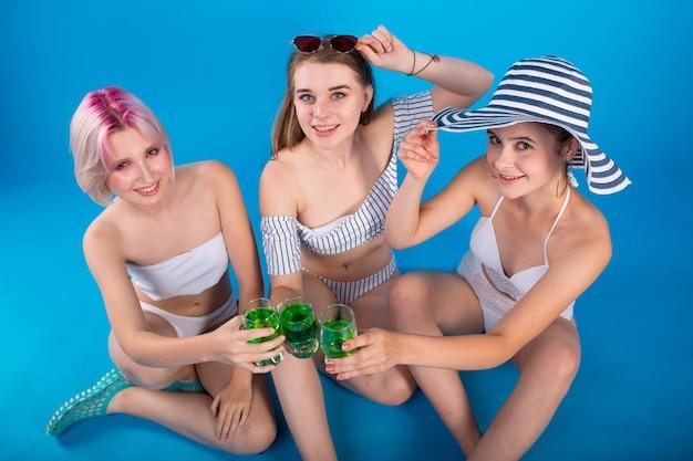 Jovem mulher três em lingerie maiô isolada em azul