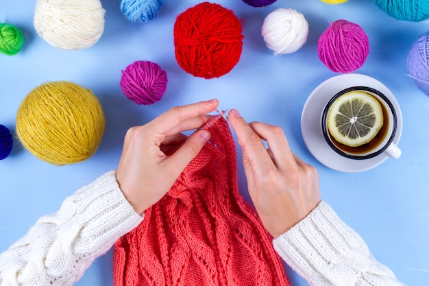 Jovem mulher tricota com agulhas de tricô