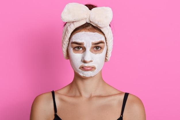 Jovem mulher triste com faixa de cabelo na cabeça e máscara cosmética no rosto, posando com beicinho, vestindo camiseta sem mangas, em pé contra um fundo rosado.