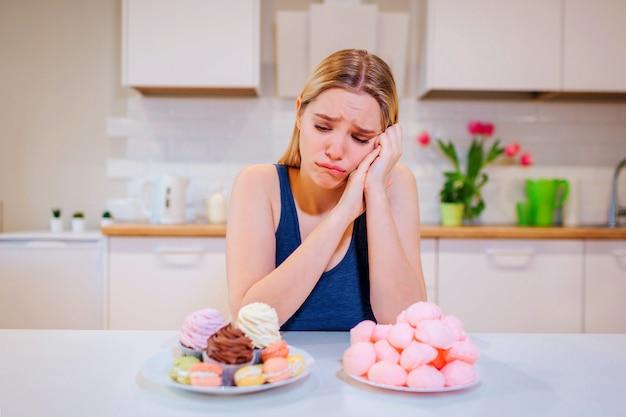 Jovem mulher triste em t-shirt azul escolhe entre frutas frescas legumes ou doces enquanto olha para eles na cozinha.