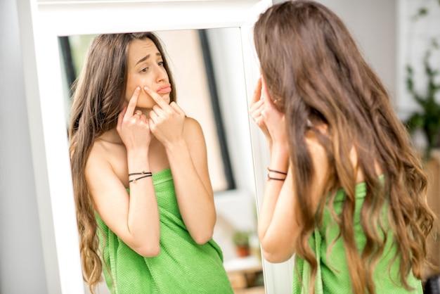 Jovem mulher triste espremendo acne se olhando no espelho do banheiro