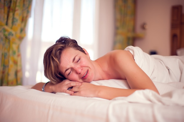 Jovem mulher triste está deitada em sua cama e chorando. conceito de pessoas e estilo de vida