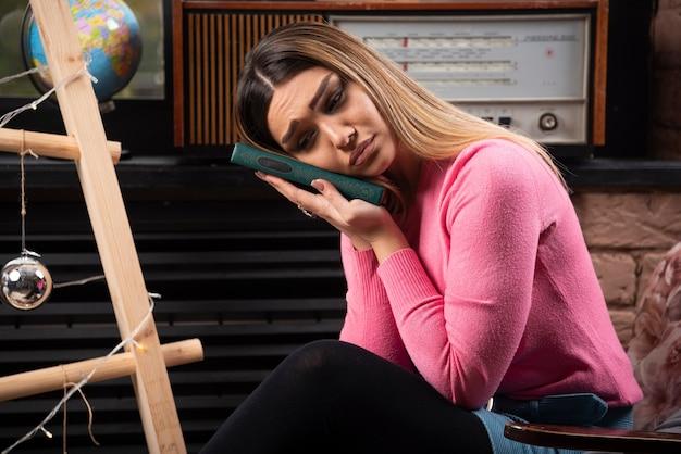 Jovem mulher triste segurando um livro em casa