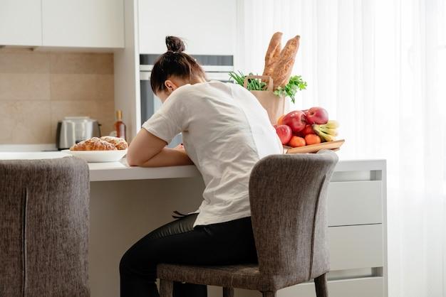 Jovem mulher triste, sofrendo na cozinha, dona de casa estressada na cozinha
