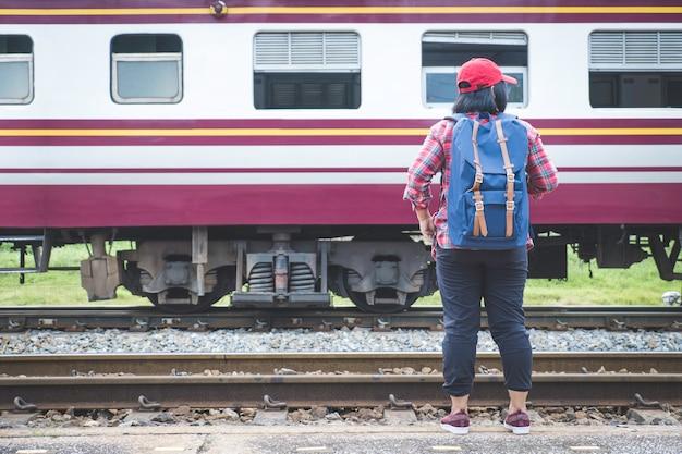Jovem mulher turismo permanente na plataforma da estação de trem