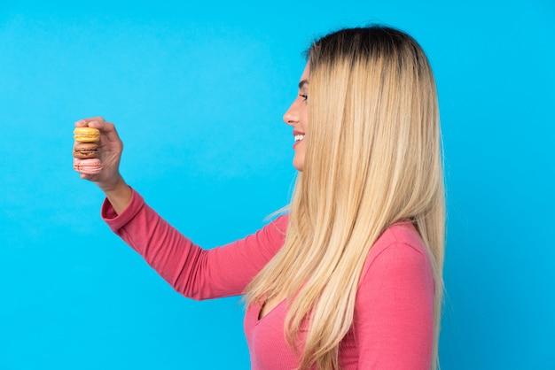 Jovem mulher uruguaia sobre parede azul isolada, segurando feliz macarons franceses coloridos e feliz