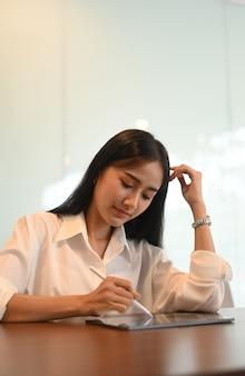Jovem mulher usando a caneta stylus, planejando seu projeto no tablet digital em um escritório mínimo.