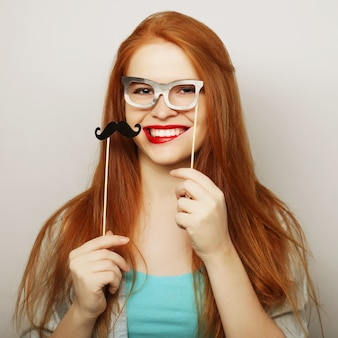 Jovem mulher usando bigodes falsos.