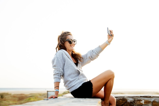 Jovem mulher usando celular móvel na zona costeira.