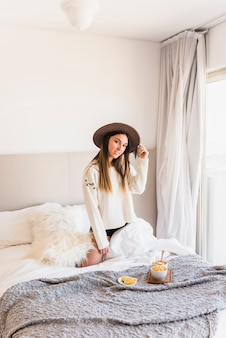 Jovem mulher usando chapéu ajoelhado na cama com café da manhã no quarto