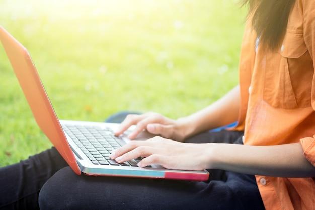 Jovem, mulher, usando computador em óculos verdes no parque.