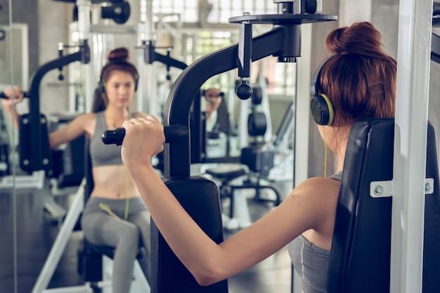 Jovem mulher usando equipamento de levantamento de peso para construir um enorme peito e braço no ginásio de esporte indoor.