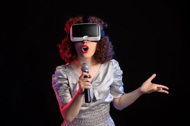 Jovem mulher usando fone de ouvido de realidade virtual com microfone e videoclipe musical
