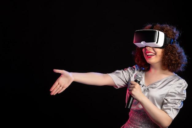 Jovem mulher usando fone de ouvido de realidade virtual com microfone em superfície escura