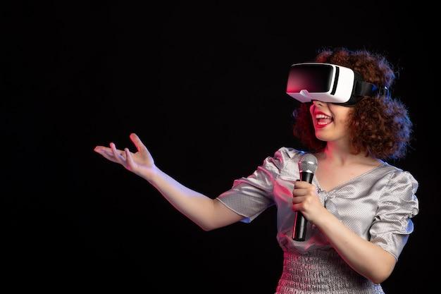 Jovem mulher usando fone de ouvido de realidade virtual com música de tecnologia de jogos de microfone