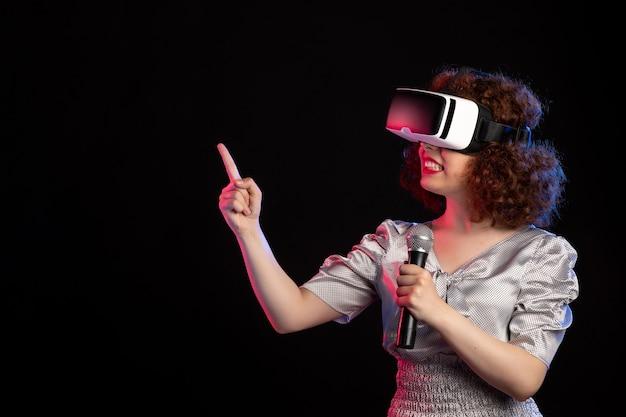Jovem mulher usando fone de ouvido de realidade virtual com música de vídeo de tecnologia de jogos de microfone