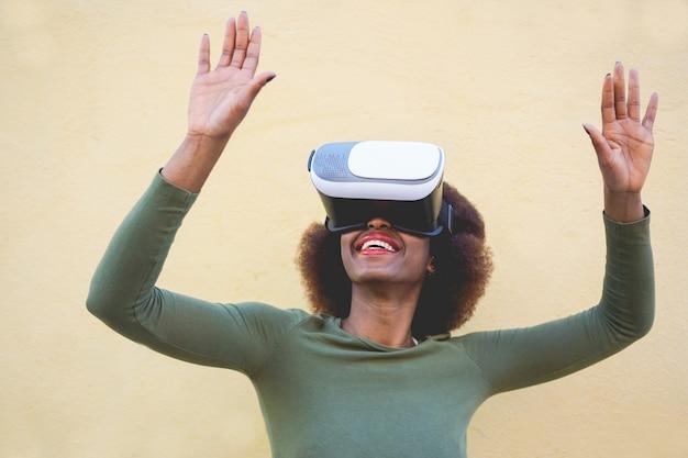 Jovem mulher usando fone de ouvido de realidade virtual com parede amarela no fundo - mulher africana se divertindo com a nova tecnologia de tendência - tecnologia, diversão e futuro conceito - foco na boca da menina e óculos vr