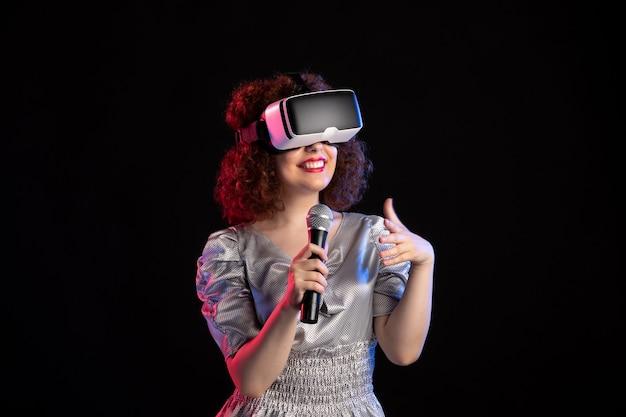 Jovem mulher usando fone de ouvido de realidade virtual com vídeo de tecnologia de jogos de música em microfone