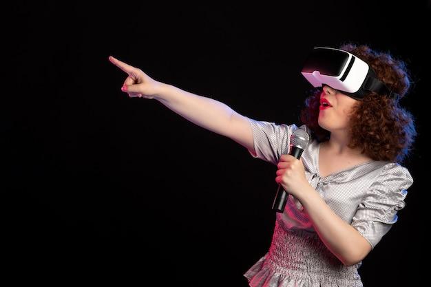 Jovem mulher usando fone de ouvido de realidade virtual com vídeos de tecnologia de música para jogos de microfone