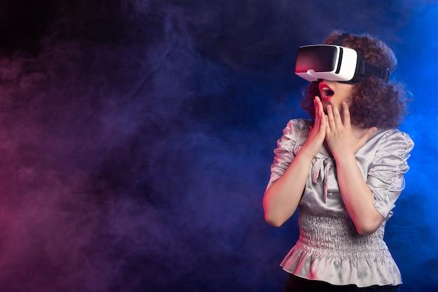 Jovem mulher usando fone de ouvido de realidade virtual em vídeo de reprodução esfumaçado escuro