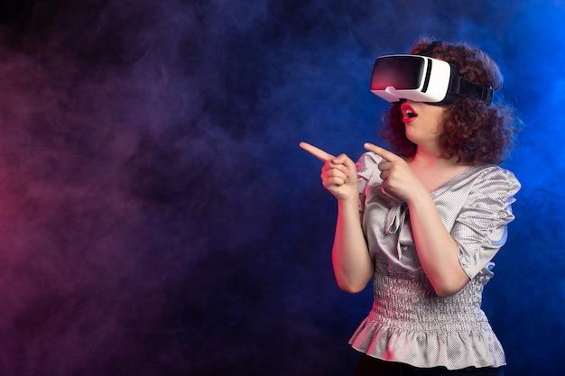 Jovem mulher usando fone de ouvido de realidade virtual no escuro esfumaçado joga videogame d
