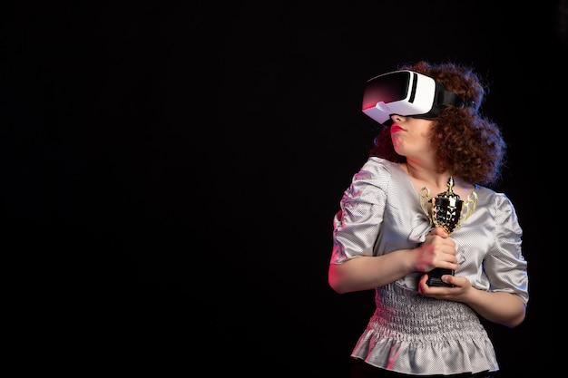 Jovem mulher usando fone de ouvido vr com copo na superfície escura, visão de jogo de videogame