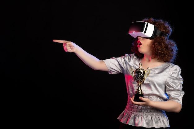 Jovem mulher usando fone de ouvido vr com copo no escuro jogo de vídeo-visão