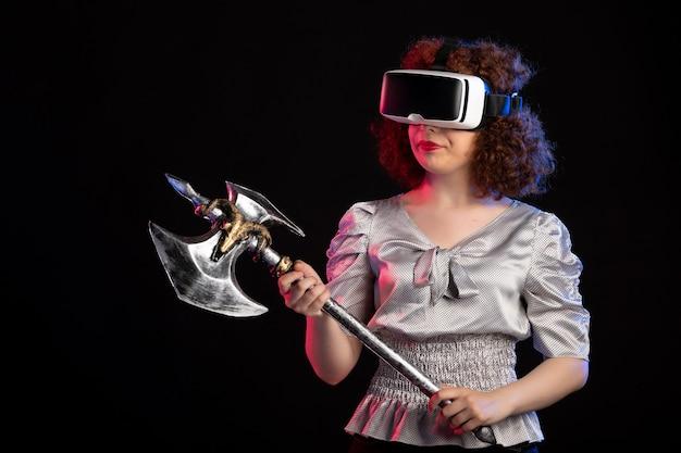 Jovem mulher usando fone de ouvido vr com machado de batalha na superfície escura