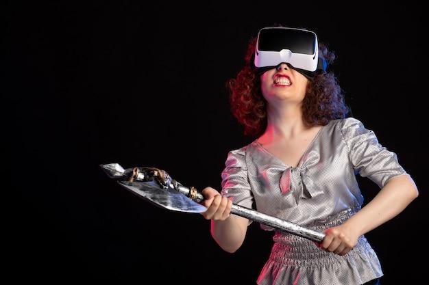 Jovem mulher usando fone de ouvido vr com machado de batalha na superfície escura.