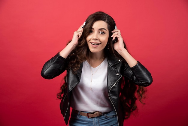 Jovem mulher usando fones de ouvido e posando em um fundo vermelho. foto de alta qualidade
